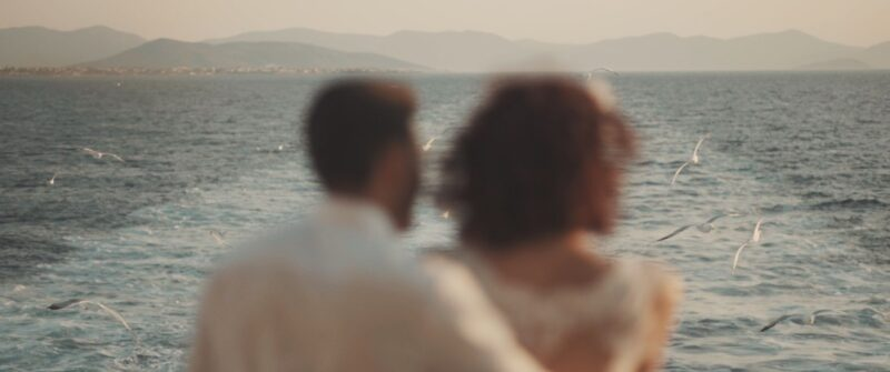 A beautiful couple is staring at the seagulls. Greek boho wedding in Aigina island | whitefilming